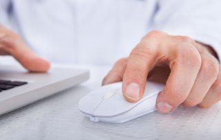 Fotografia-closeup-mão-de-doutor-movendo-mouse-sentado-frente-ao-computador