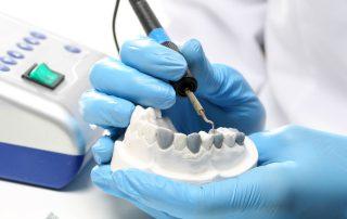 fotografia-das-mãos-de-protético-enquanto-realiza-processo-de-enceramento-e-escultura-dental