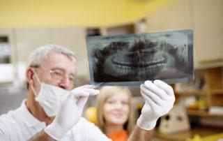 fotografia-de-dentista-mostrando-raiox-dos-dentes-para-paciente