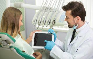 fotografia-de-dentista-sorridente-mostrando-informações-no-tablet-para-paciente-em-consultório-odontológico