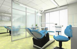 fotografia-do-Interior-de-um-gabinete-odontológico-separado-por-divisória-de-vidro-contendo-mesa-cadeira-e-instrumentos-odontológicos-azul-ambiente-iluminado-e-higiênico.