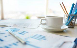 fotografia-mesa-de-escritório-com-foco-em-xícara-e-porta-canetas.-sobre-a-mesa-há-prancheta-com-gráficos-estatísticos-em-azul